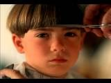 Close Up Tilt Up Hand Of Barber Cutting Bangs Over Eyes Of Pouting Young Boy